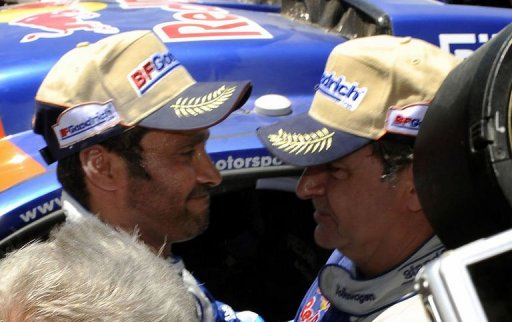 Le pilote Carlos Sainz (D) félicite le pilote du Qatar Nasser Al-Attiyah à Baradero, en Argentine, le 15 janvier 2011